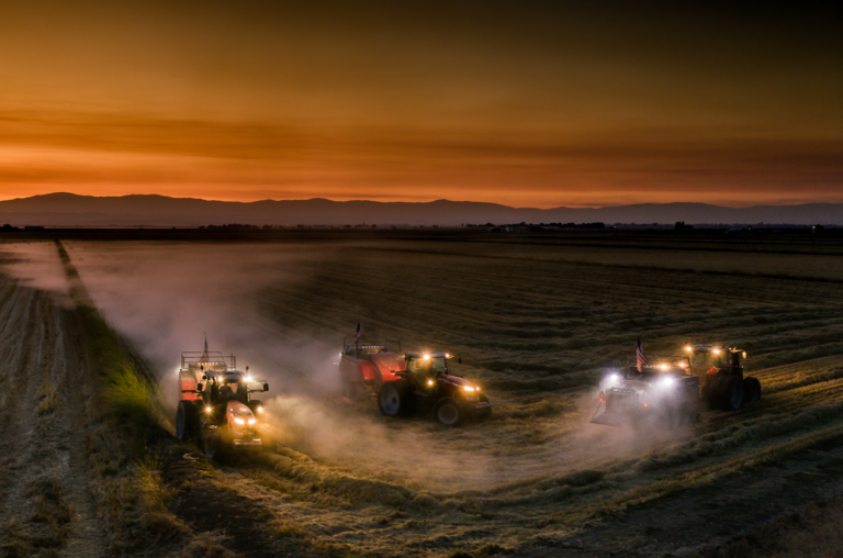 3 tractors in a rice field at sunrise